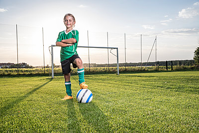 Portrait of confident young football player with ball on football ground - p300m1581752 by Fotoagentur WESTEND61