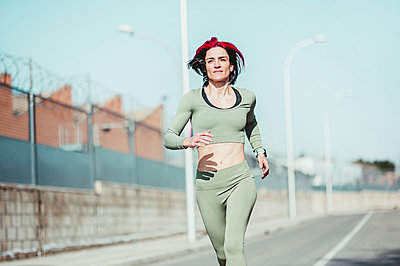 Woman with highlights running during sunny day - p300m2266392 by Jose Luis CARRASCOSA