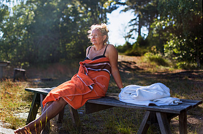 Woman wrapped in towel relaxing on bench - p312m2145822 by Pernille Tofte