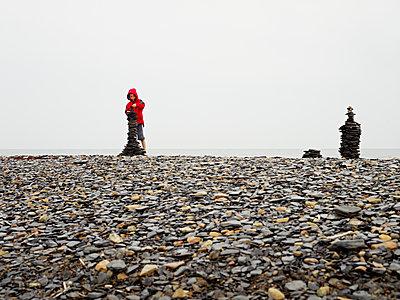 Sweden, Oland, Boy (6-7) building cairn on beach - p352m1061594f by Love Lannér