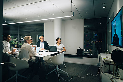 Colleagues looking at businessman during video conference meeting at night in office - p426m2194786 by Maskot