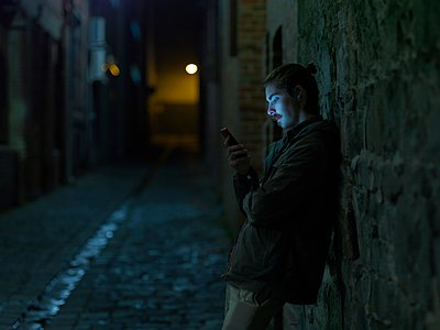Young man in street, leaning against wall, at night, using smartphone - p429m1052754 by Elke Meitzel