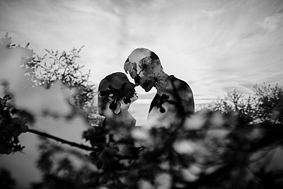 Double exposure of Caucasian couple kissing near trees - p555m1301819 by Kateryna Soroka