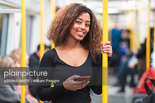 Portrait of smiling young woman with smartphone on a subway - p300m2166976 by William Perugini