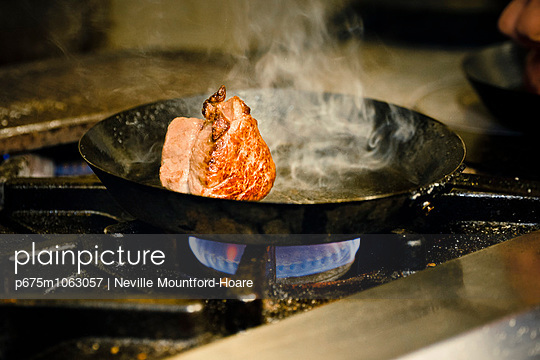 Meat cut browning in pan - p675m1063057 by Neville Mountford-Hoare