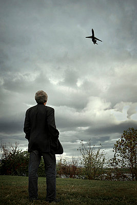 Man watching airplane - p1019m739843 by Stephen Carroll