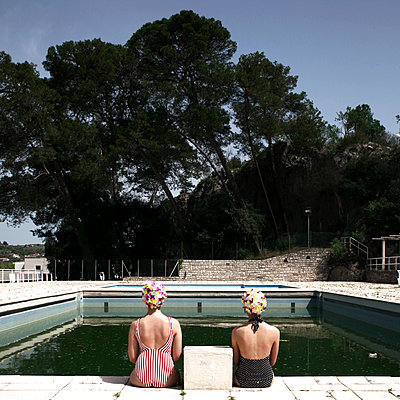 Two girlfriends sitting at the edge of outdoor pool - p1105m2082591 by Virginie Plauchut