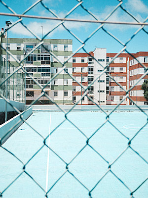 Blue football soccer court through fence with buildings in background - p1166m2129959 by Cavan Images
