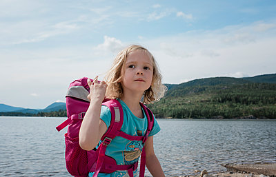 portrait of a young girl hiking with a backpack by the sea - p1166m2138064 by Cavan Images