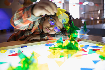 Curious boy playing with shapes at lighted display in science center - p1192m1194228 by Hero Images