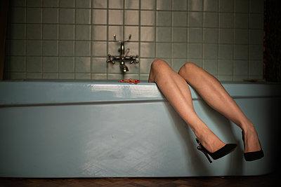 Female legs placed on bathtub edge - p1321m2223425 by Gordon Spooner