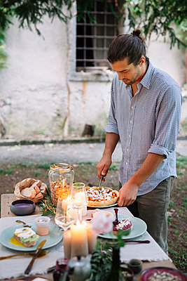 Man arranging a romantic candelight meal outdoors - p300m2068371 by Alberto Bogo