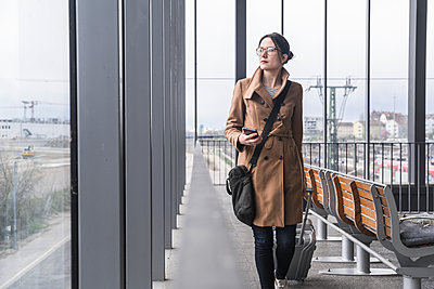 Businesswoman walking with baggage and cell phone - p300m2104435 von Uwe Umstätter