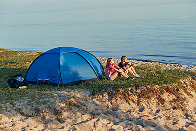 Young couple relaxing near tent - p312m1522174 by Johan Alp