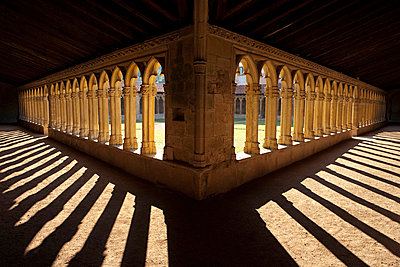 Charlieu Abbey with strong sunlight through stone arches in France - p3313575 by Andrea Alborno