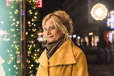 Mature woman christmas window shopping at night, Munich, Germany - p429m1227124 by William Perugini