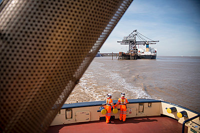 Workers on tug boat overlooking crane - p429m726931f by Monty Rakusen