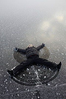 Girl lying on snow and making snow angel - p5756594 by Tove, Jan