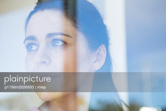 Frau blickt aus dem Fenster - p1156m2026933 von miep