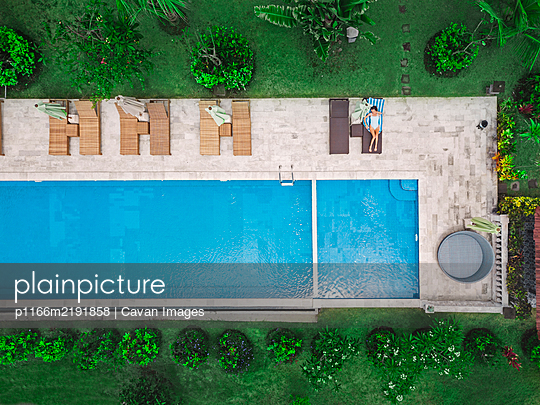 Aerial view of attractive woman near the pool at resort - p1166m2191858 by Cavan Images