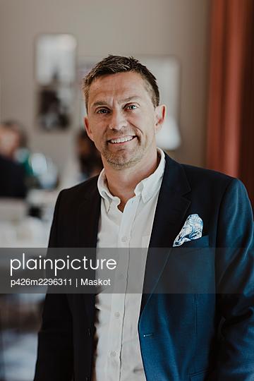 Portrait of smiling male entrepreneur at corporate office - p426m2296311 by Maskot