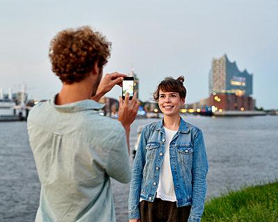 Mann fotografiert Frau mit Smartphone an der Elbe - p1124m1150185 von Willing-Holtz