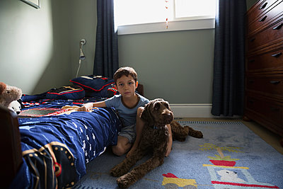 Portrait serious boy with dog on bedroom floor - p1192m1078232f by Hero Images