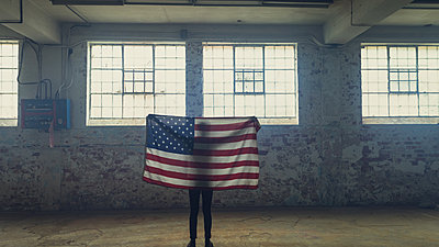 Young man holding an American flag inside an empty warehouse - p1315m2130317 by Wavebreak