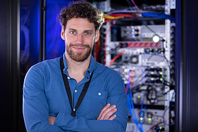 Male IT specialist with arms crossed standing in data center - p300m2275198 by Florian Küttler