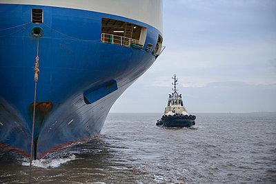 Tugboat sailing by large ship - p429m747080f by Monty Rakusen