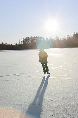 A woman skating on a frozen lake - p5754819 by Peter Rutherhagen