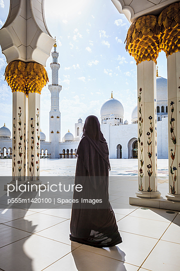 Woman walking at Sheikh Zayed Grand Mosque, Abu Dhabi, United Arab Emirates - p555m1420100 by Spaces Images