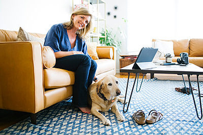 Woman stroking Labrador Retriever in living room - p1427m1504484 by Jessica Peterson