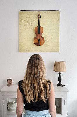 Girl looking at a violin - p1515m2093183 by Daniel K.B. Schmidt