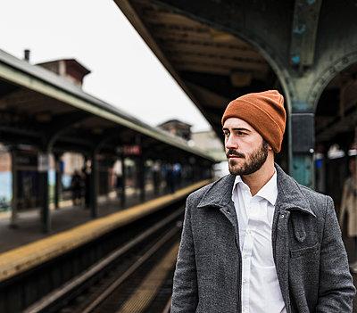 Young man waiting at metro station platform - p300m1191555 by Uwe Umstätter