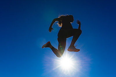 Sportive young woman jumping under blue sky in backlight - p300m2059930 von Francesco Morandini