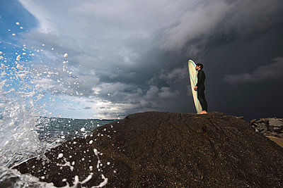 Man standing on rock with his surfboard against cloudy sky - p3071225f by Maurizio  Borsari