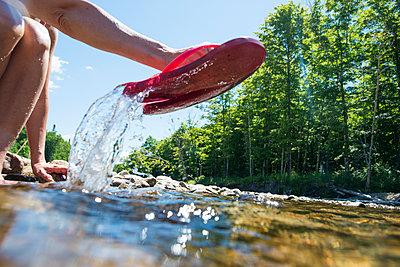 Pink flip flops in the river - p343m1218083 by Joe Klementovich
