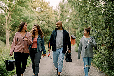 Smiling daughters with father and mother on footpath during vacations - p426m2227835 by Maskot