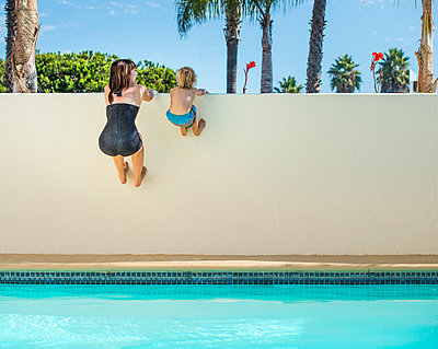 Mother and son holding onto poolside wall, Los Angeles, California, USA - p429m999697 by JLPH