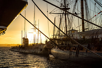 Ship and sailboat in the harbour at sunset; San Diego, California, United States of America - p442m1580408 by Aaron Von Hagen