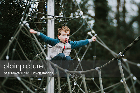 Side view of boy balancing on climbing frame looking into distance - p1166m2130792 by Cavan Images