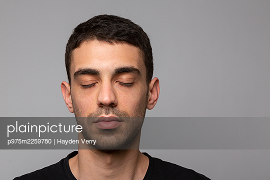 Young man with closed eyes, portrait - p975m2259780 by Hayden Verry