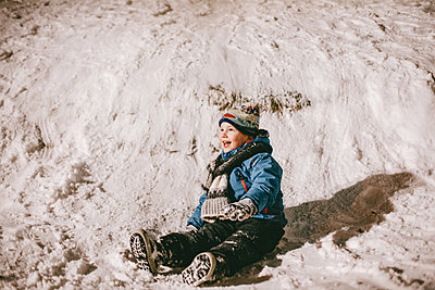 Cheerful boy sitting on snow beside hill in winter - p1166m2141046 by Cavan Images