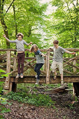 Drei Jungen springen von Holzbrücke - p1195m1138122 von Kathrin Brunnhofer