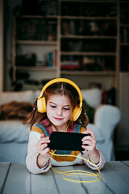 Girl wearing headphones using mobile phone while standing at home - p300m2225556 by Eva Blanco