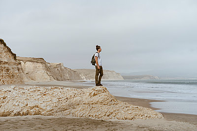 Man standing on rock at beach in Point Reyes, California, USA - p300m2290454 by VITTA GALLERY