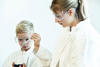 Brother and sister wearing safety goggles doing science experiment - p429m803672f by Sigrid Gombert