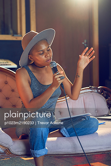 Female musician singing into microphone in recording studio - p1023m2190233 by Trevor Adeline
