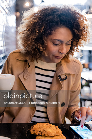 Woman using cell phone in a cafe - p300m2103320 by Francesco Morandini